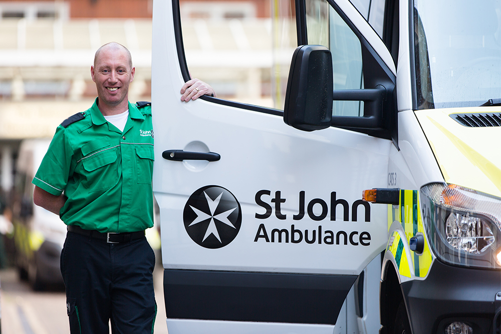 St John Ambulance male ambulance driver stands next to a open ambulance door