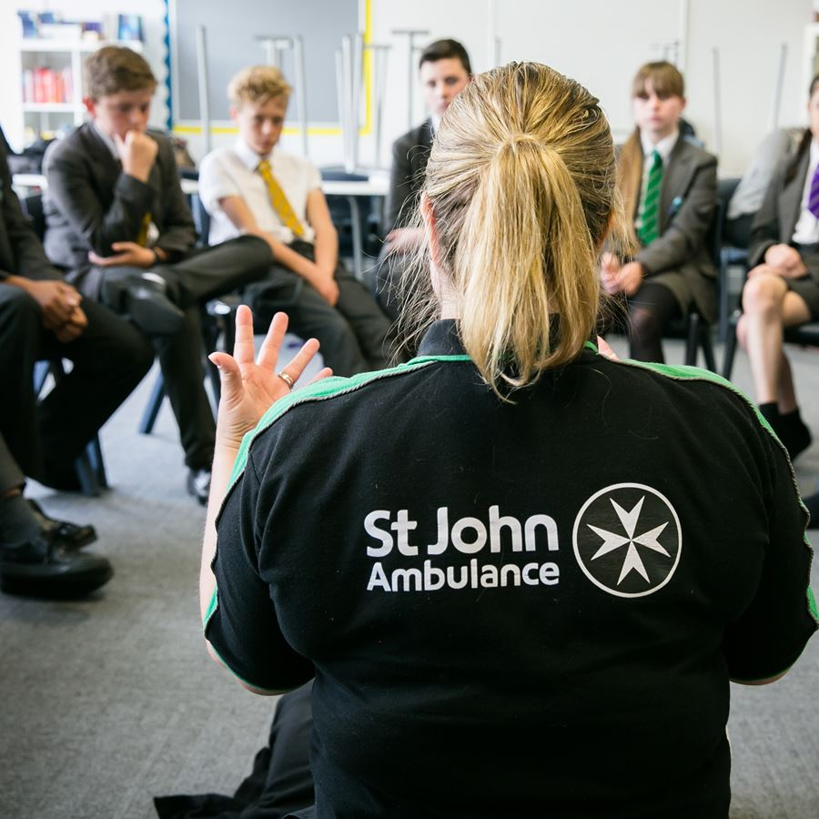 A St John Ambulance trainer teaching a class of students first aid