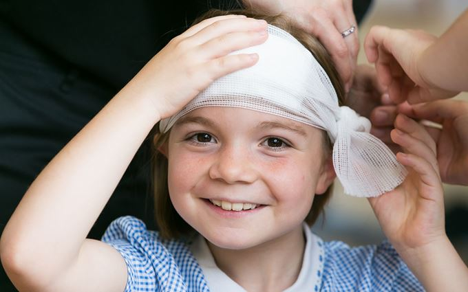 School child with bandage around head