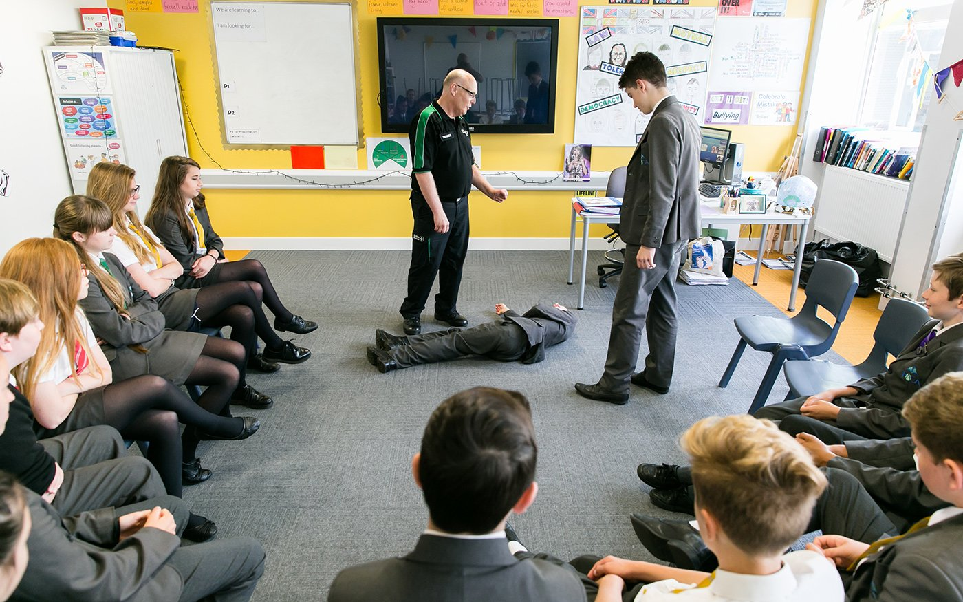 School pupils learning emergency first aid