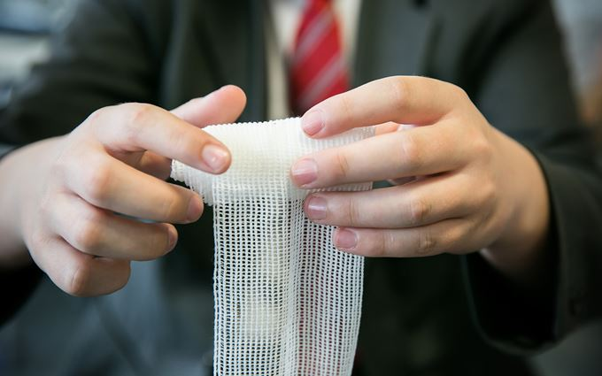 School pupils learning to bandage a wound