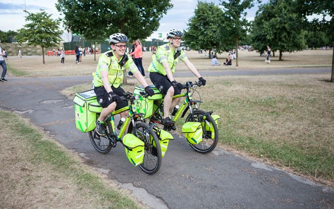 Pair of Emergency Cycle Responders cycling through a park