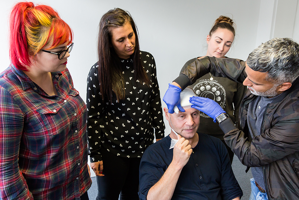 Delegates learning how to apply a head bandage