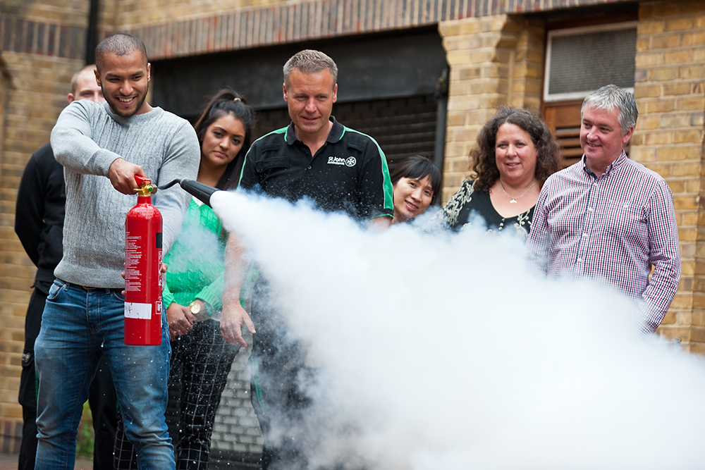 Group observes course delegate practising with a fire extinguisher