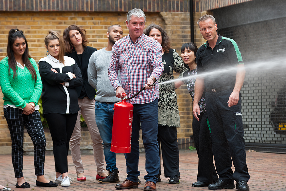 Course group watches demonstration of using a fire extinguisher