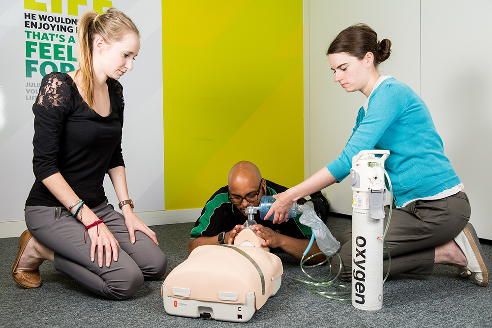 Course students practise application of medical gas to manikin, supported by St John Ambulance trainer