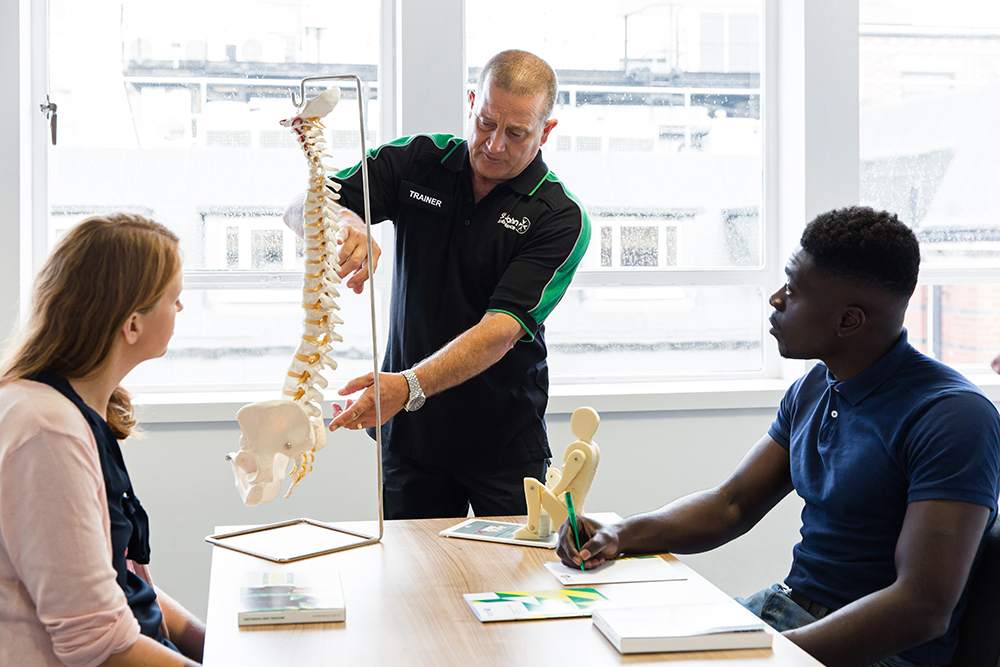 Students learn about spinal anatomy with support from a St John Ambulance trainer