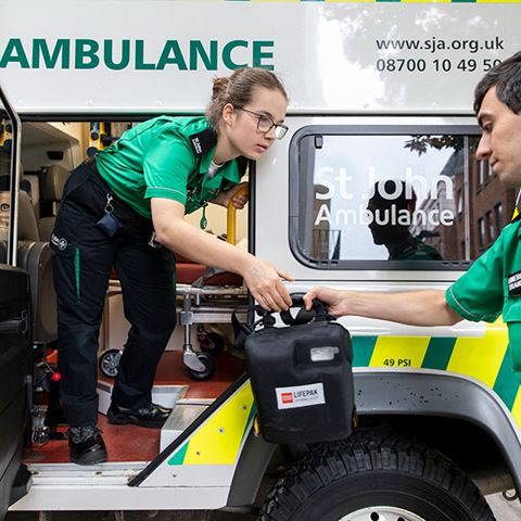 A volunteer standing in an ambulance passing a defibrillator to another volunteer.