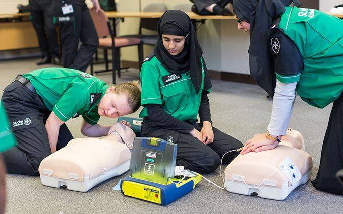 3 cadets practising doing CPR and using a defibrillator on a training manikin.