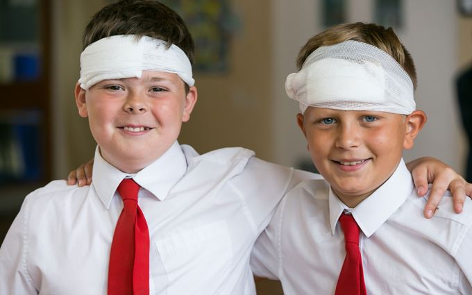 Two school children with bandages on their heads