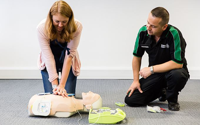 St John Ambulance class participant practicing CPR using a training mannequin