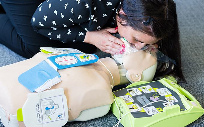 Class participant practices resuscitation using a training mannequin