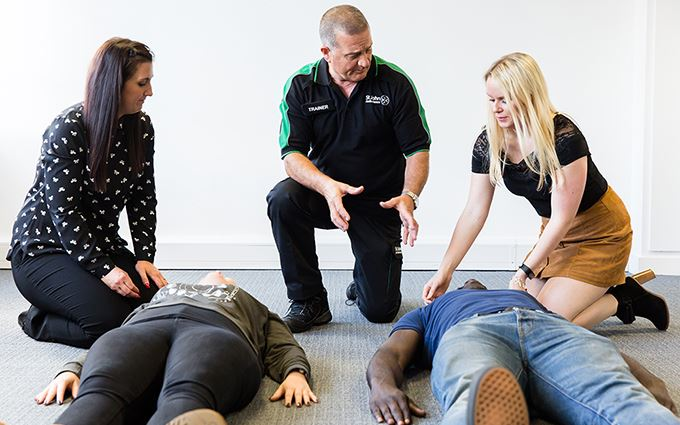 First aid course participants learning how to put someone in the recovery position