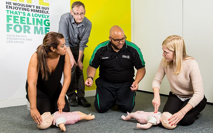 First aid course participants practicing baby CPR on a training mannequin