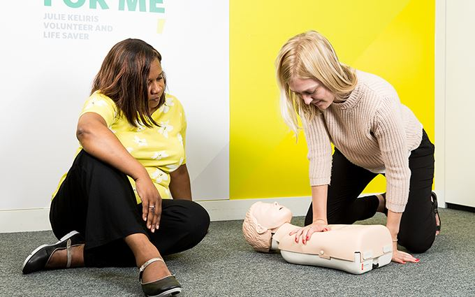 First aid class participants practicing child CPR using a training mannequin