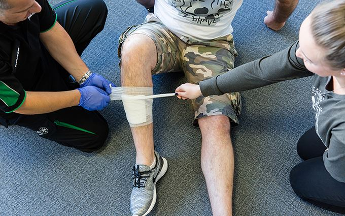 First aiders practicing bandaging a leg
