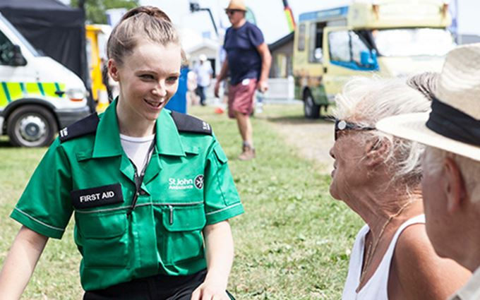 First aider attending elderly couple at outdoor event